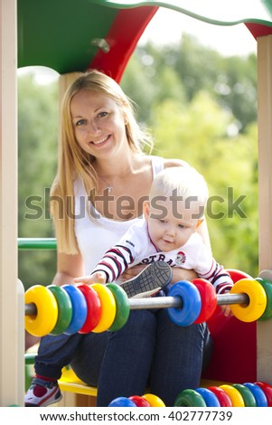 Young mother with two year old son on the playground - stock photo