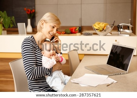 Young mother working from home, holding baby on lap. - stock photo