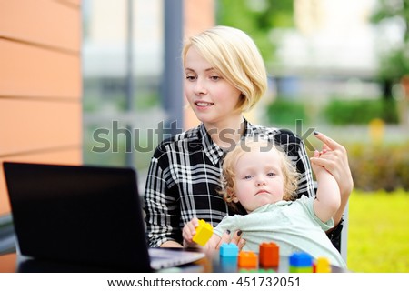 Young mother working oh her laptop and holding her sad toddler daughter