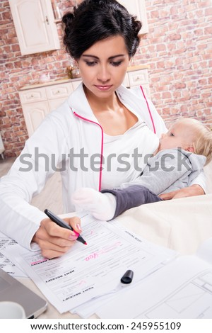 Young mother working while breastfeeding her baby