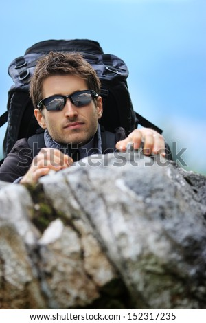 Young mountain climber with sunglasses scaling a cliff, focus on face - stock photo