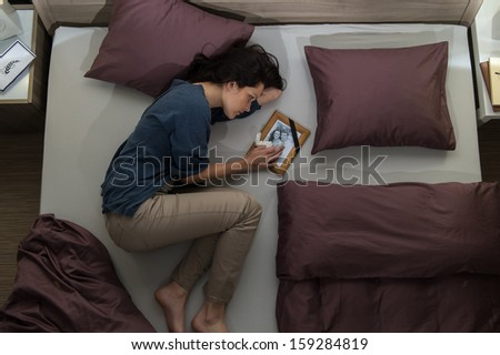Young mourning woman lying in bed alone - stock photo