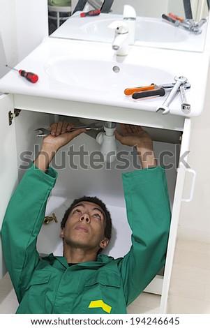 Young mulatto plumber repairing sink in kitchen.  - stock photo
