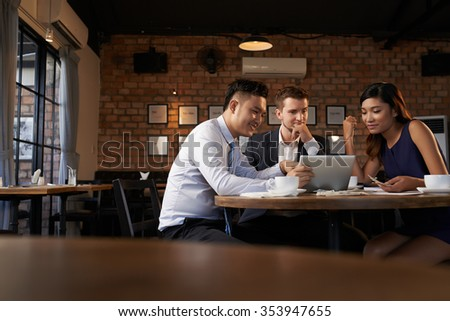 Young multi-ethnic business team sharing ideas in a cafe