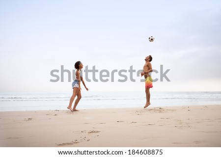 Young multicultural couple playing football on beach
