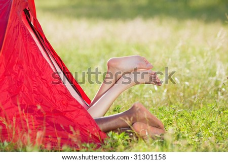 young multiethnic couple lying in tent with feet crossed. Copy space - stock photo
