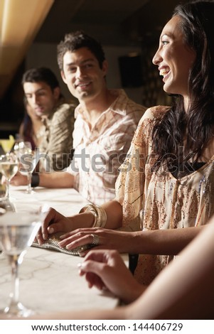 Young multiethnic group at the bar with cocktail glasses - stock photo