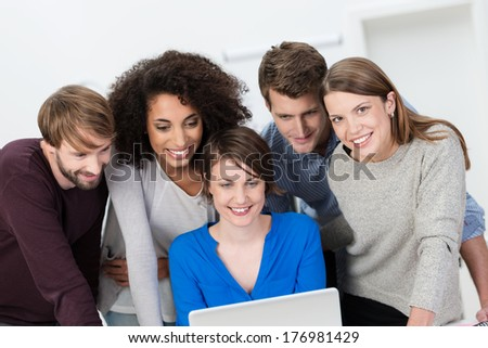 Young multiethnis business team working together standing clustered around a laptop computer having a brainstorming session - stock photo