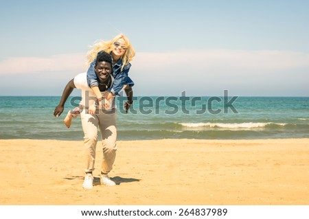Young multiracial couple at the beach having fun with piggyback jump - Happy mixed race boyfriend and girlfriend playing at the beginning of love story - Multi ethnic integration love against racism  - stock photo