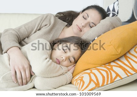 Young mum and daughter sleeping on a sofa at home. - stock photo