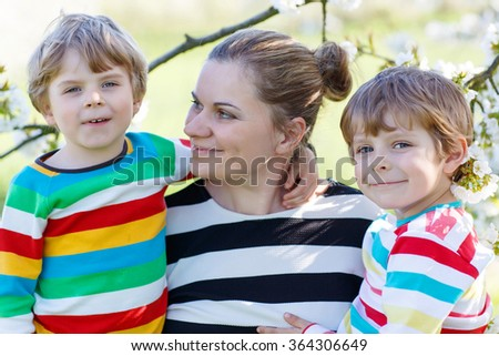 Young mum and two little sibling kids having fun on blooming cherry garden in spring. Happy family enjoying nature, togetherness and celebrating mother's day. - stock photo