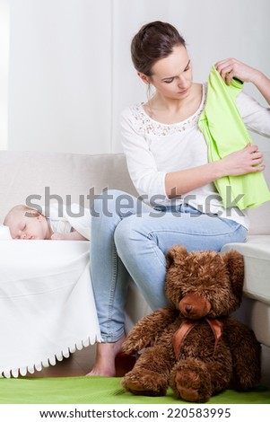 Young mum cleaning room and sleeping baby - stock photo