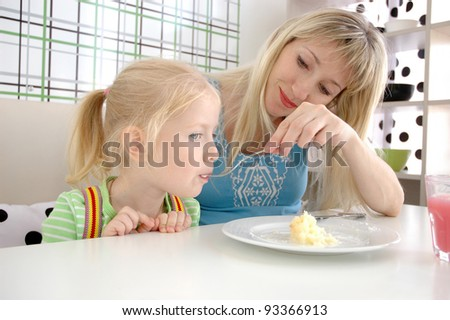 Young mum feeds the daughter with a potato in cafe - stock photo