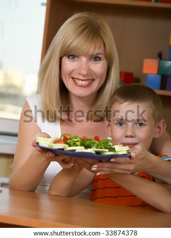 Young mum is with the small son green salad - stock photo