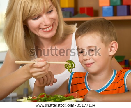 Young mum is with the small son green salad
