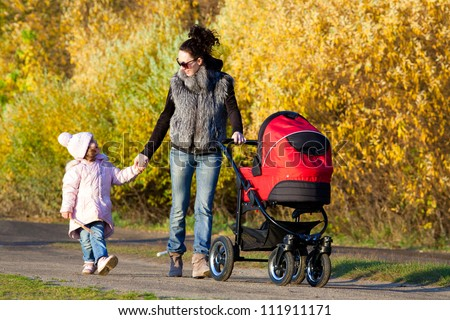 Young mum walks with children in the autumn park