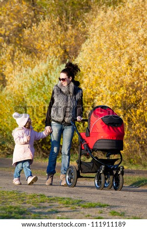 Young mum walks with children in the autumn park - stock photo