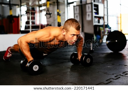 Young muscular athlete doing pushups - stock photo