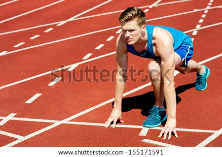 Young muscular athlete is at the start of the race