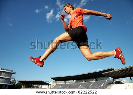 young muscular athlete is running  at the stadium background of blue sky - stock photo
