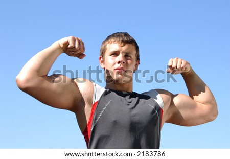 Young muscular athlete showing his biceps - stock photo