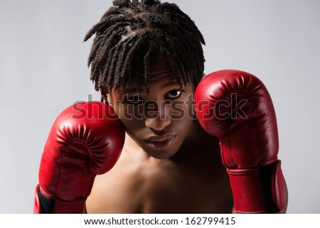 Young muscular athletic male boxer wearing blue boxing shorts and red boxing gloves. Fighter is on a grey background. - stock photo