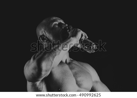 Young muscular bodybuilder posing over black background