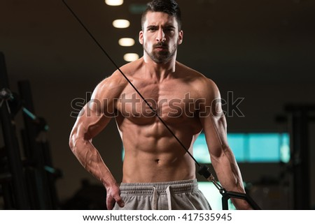 Young Muscular Fitness Bodybuilder Doing Heavy Weight Exercise For Triceps In The Gym - stock photo
