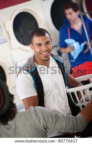 Young muscular Latino man smiles in laundromat - stock photo