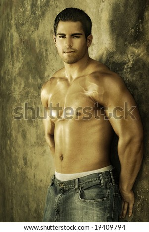 Young muscular male against wall with golden light - stock photo