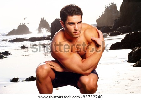 Young muscular male bodybuilder on the beach - stock photo
