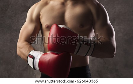 Young muscular man boxer, boxing gloves