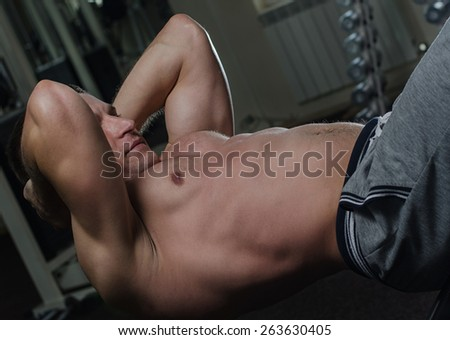 Young muscular man doing abdominal exercises in the gym. Highlight the background. - stock photo