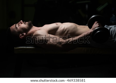 Young Muscular Man Doing Heavy Weight Exercise For Forearm With Dumbbells In Gym