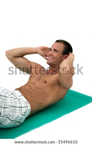 Young muscular man doing sit up exercises on mat - stock photo