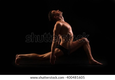 young muscular man doing yoga, fitness, gymnastics. deep attack and deflection