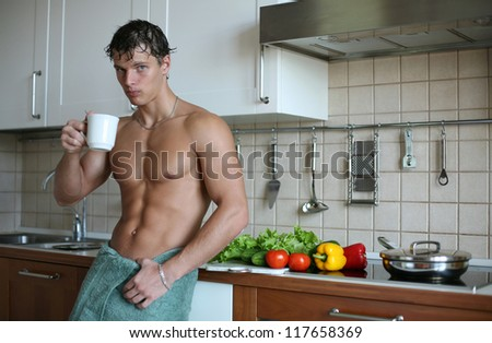 Young muscular man drinking tea at the kitchen - stock photo