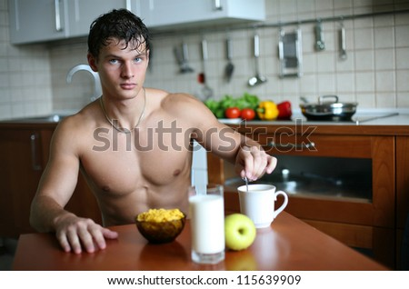 Young muscular man eating his breakfast at the kitchen - stock photo
