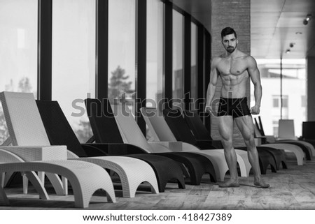 Young Muscular Man Flexing Muscles By Swimming Pool And Sun Loungers - stock photo
