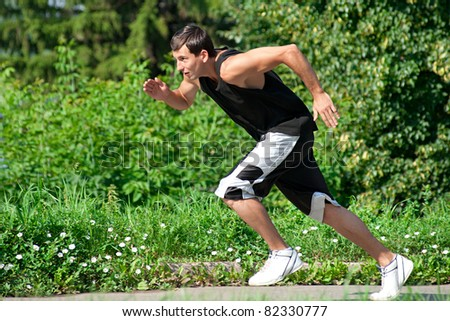 Young muscular man jogging in park