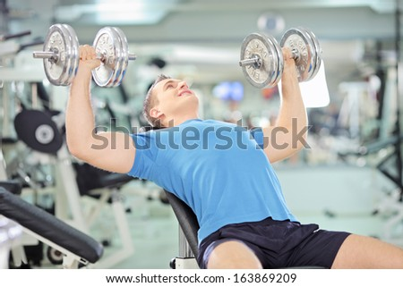 Young muscular man lifting weights in a gym - stock photo
