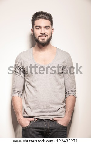 young muscular man looking away while standing close to his girlfriend, studio shot on gray background - stock photo