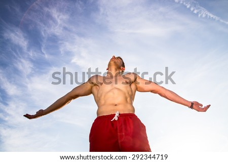 young muscular man outstreched hands under the sky