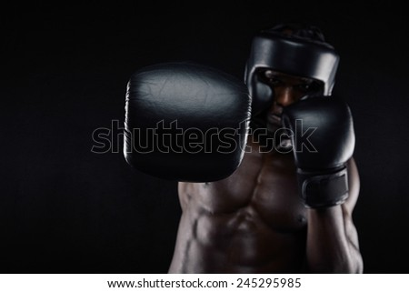 Young muscular man practicing boxing. African male throwing punch towards camera against black background. Fit young man in boxing gear exercising. - stock photo