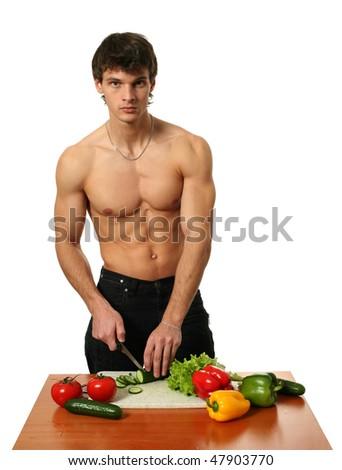 Young muscular man preparing salad isolated on white