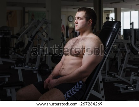 Young muscular man resting after exercise in the gym
