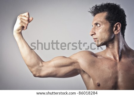 Young muscular man showing his biceps - stock photo