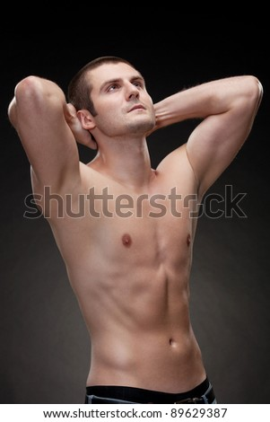 Young muscular man showing his muscles - stock photo