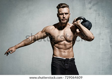 Young muscular man training with kettlebell. Photo of man with naked torso on grey background. Strength and motivation