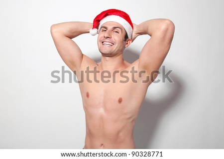 Young muscular man wearing Santa hat laughing with hands behind his head - stock photo